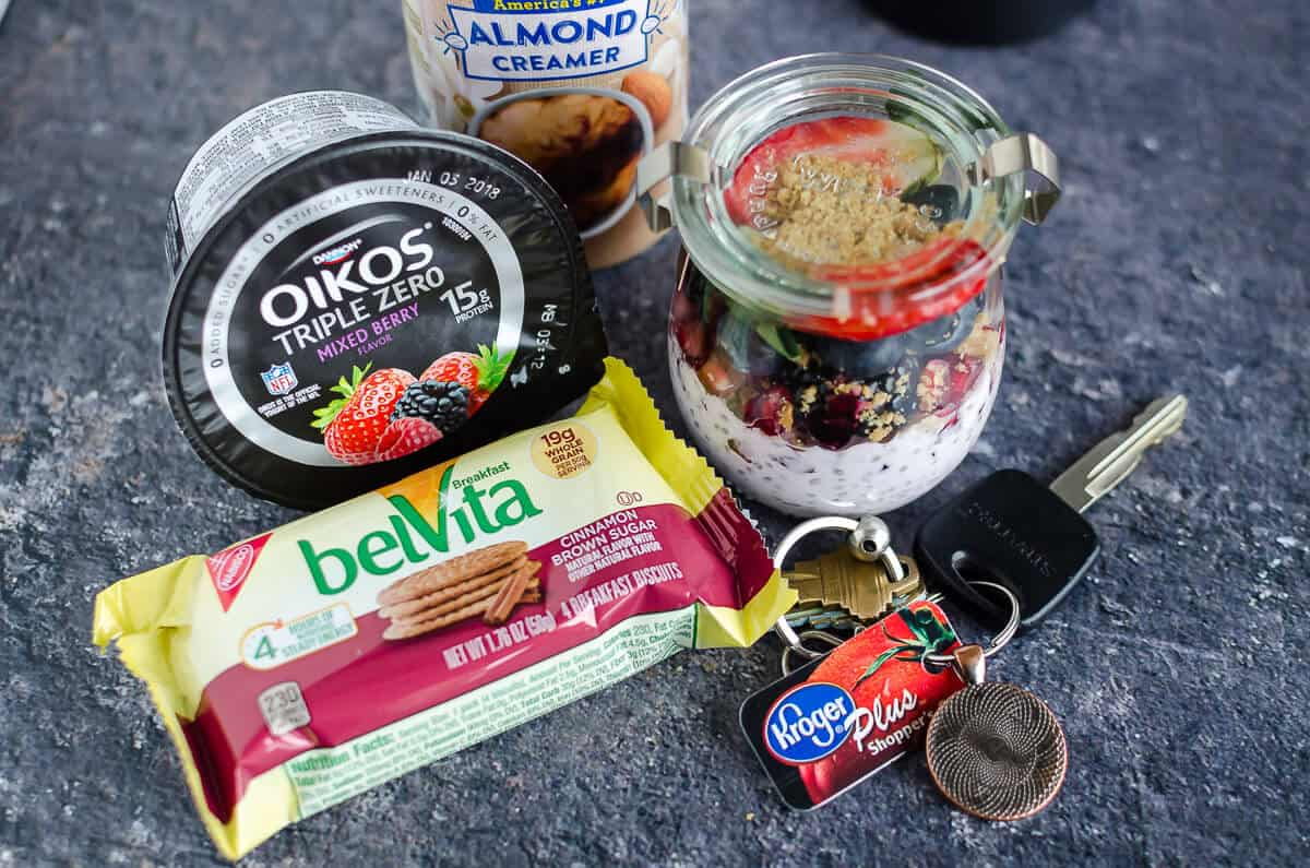 easy on the go chia seed pudding, jar layered with oikos greek yogurt chia pudding, pomegranate, fresh berries, belVita breakfast biscuts and silk creamer