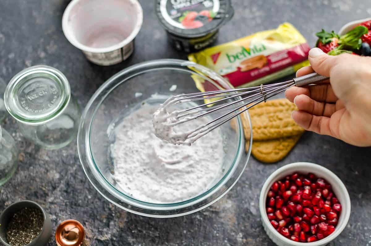 bowl of yogurt, chia seeds, almond milk being whisked together, pomegranates, belVita breakfast biscuits and oikos yogurt off to the side