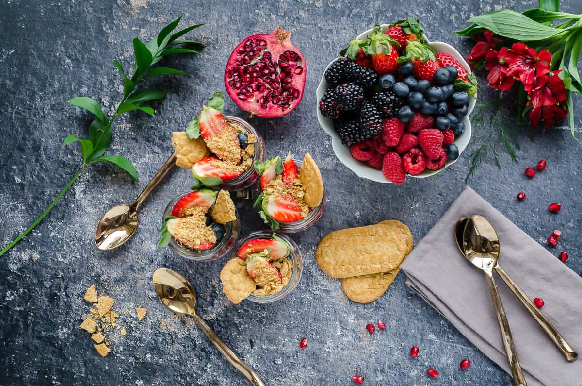 4 jars chia breakfast pudding topped with fruit, bowl of fresh berries, gold spoons, greenery