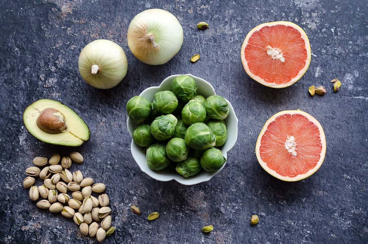 bowl for brussels sprouts, 2 grapefruit halves, 2 onions, half an avocado with the pit, some unshelled pistachios