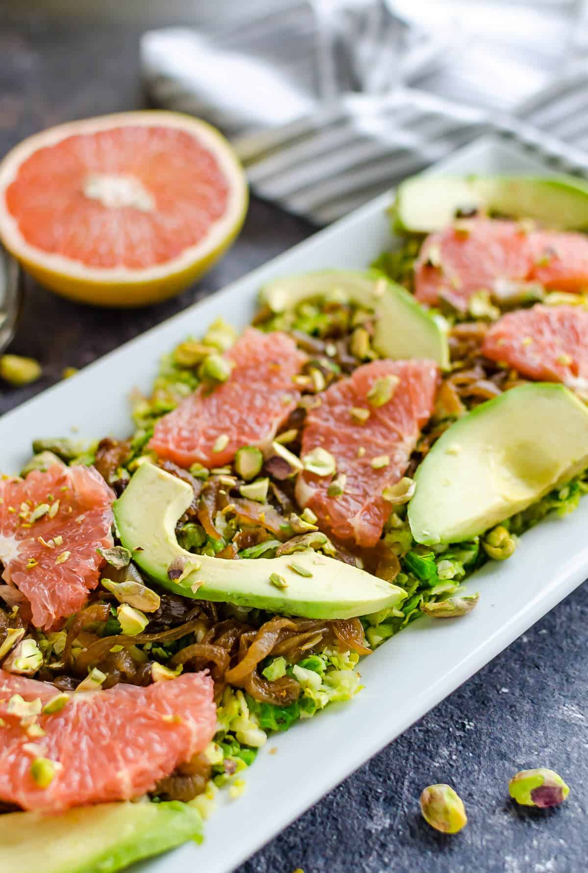 chopped brussels sprouts salad on a rectangle white platter with caramelized onions, grapefruit segments, avocado slices, and pistachios