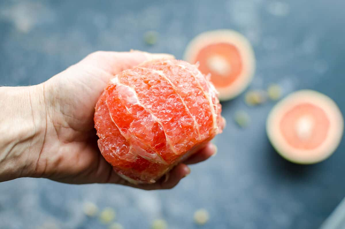 hand holding a whole peeled juicy pink grapefruit