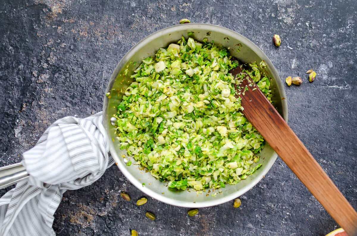 skillet with sauteed brussels sprouts, wooden spatula
