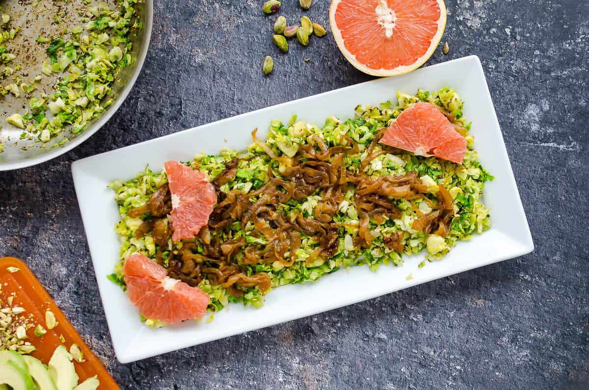 platter of chopped brussels sprouts, caramelized onions and a few grapefruit segments