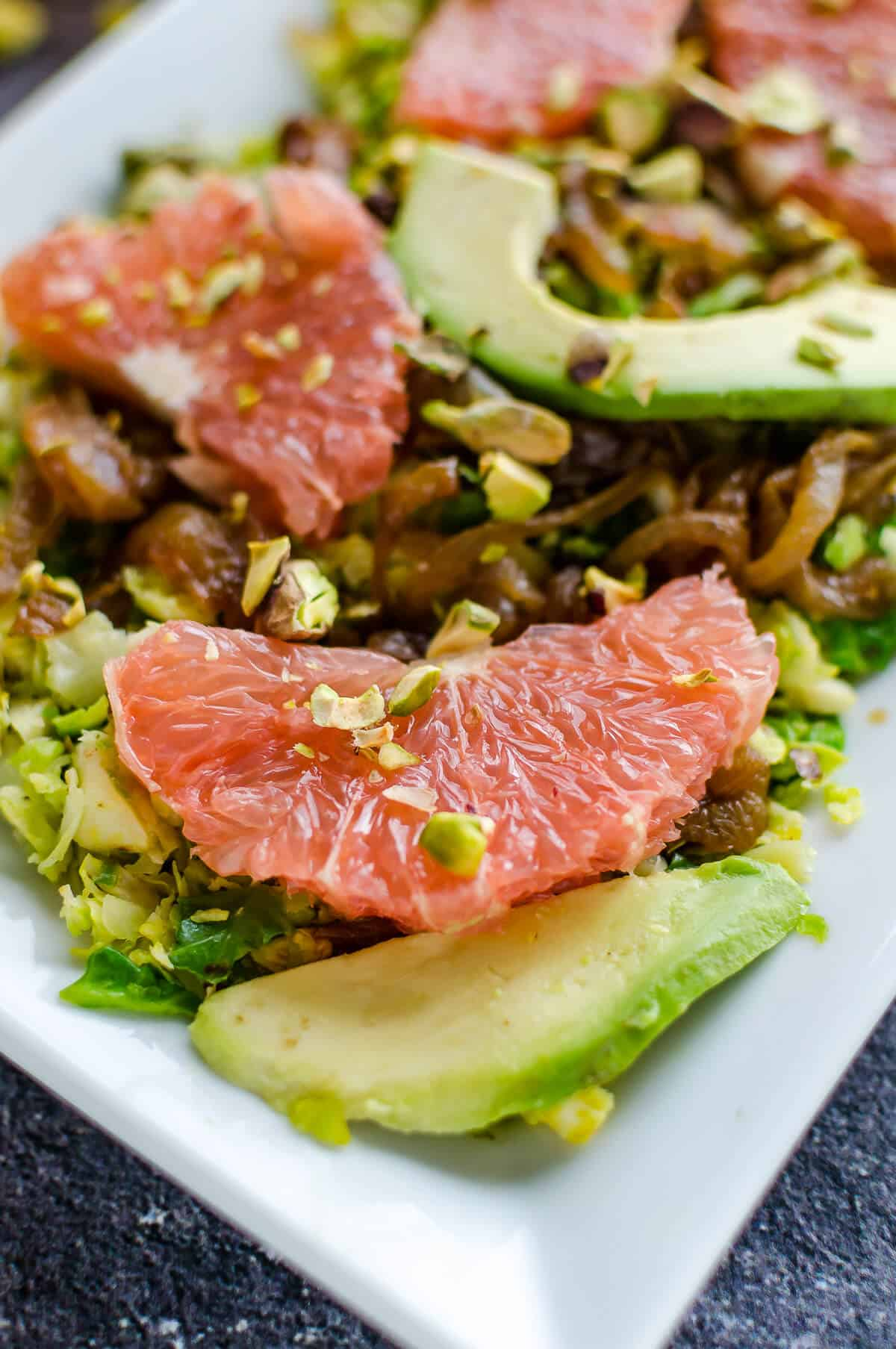 corner of platter containing chopped brussels sprouts salad with grapefruit and avocado slices