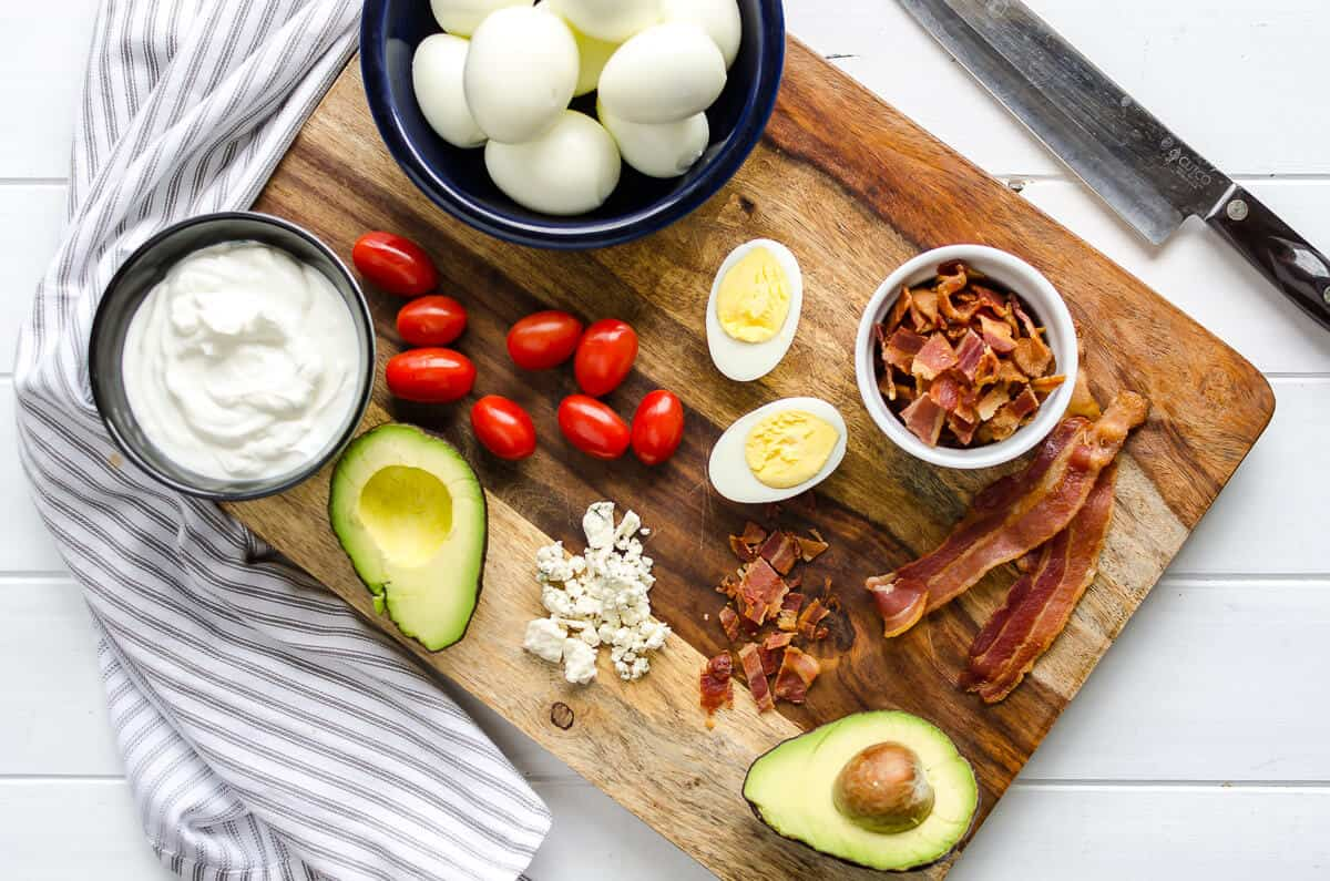 beautiful wood cutting board with cobb egg salad ingredients laid out, dark bowl full of whole hard boiled eggs, glass container of yogurt, bacon, grape tomatoes, and halved avocado