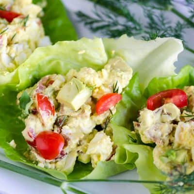 egg salad with chopped tomatoes, avocados, bacon, and blue cheese in a lettuce cup garnished with fresh dill