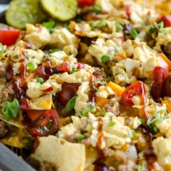 pan of bbq bacon cheeseburger nachos topped with cole slaw and barbecue sauce drizzle.