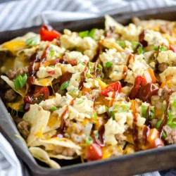 sheet pan of bbq bacon cheeseburger nachos made with ground turkey, topped with cole slaw and drizzled with bbq sauce