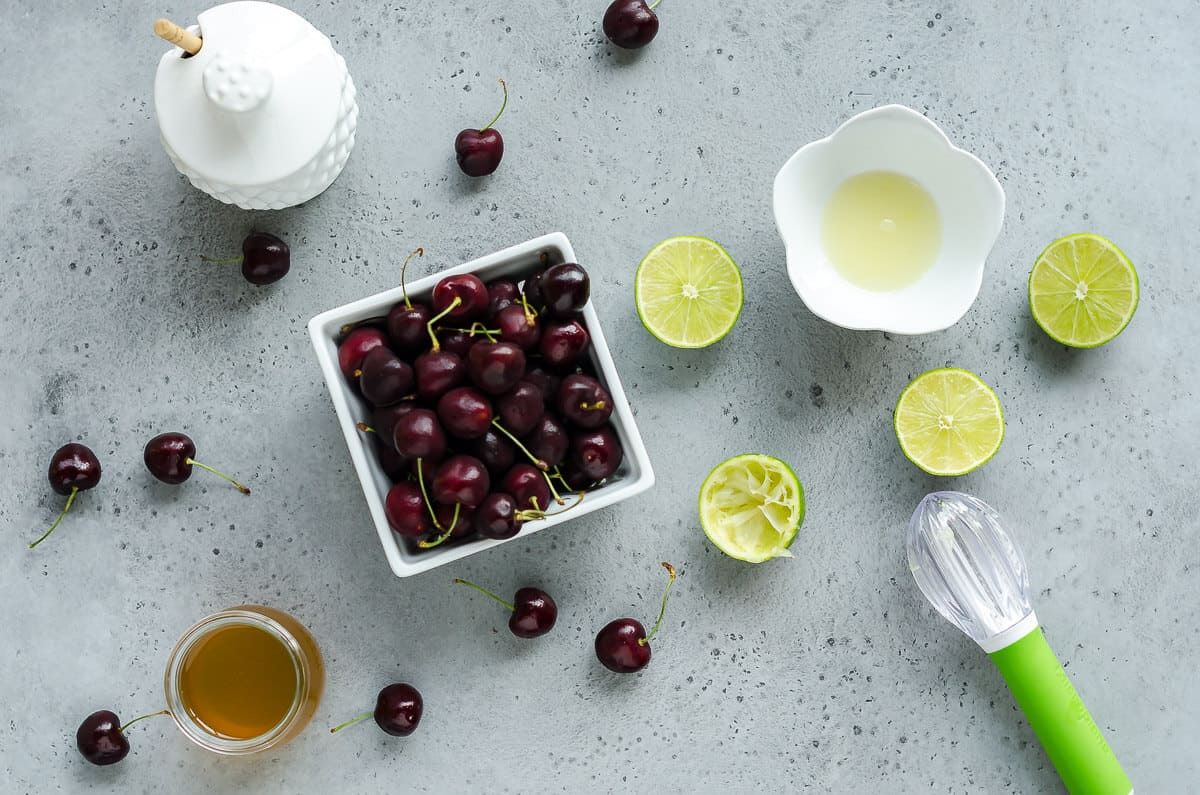ingredients for cherry cooler. quart of sweet cherries, limes, lime juice and simple syrup made with honey