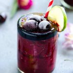 glass of deep red frozen cherry cooler garnished with sweet cherries and a lime slice. flowers in the back ground