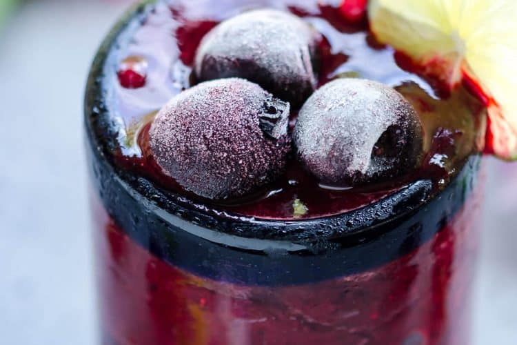 deep red frozen cherry cooler filled to the brim of a clear glass topped with frosty frozen sweet cherries and garnished with slice of lime on the side of the glass