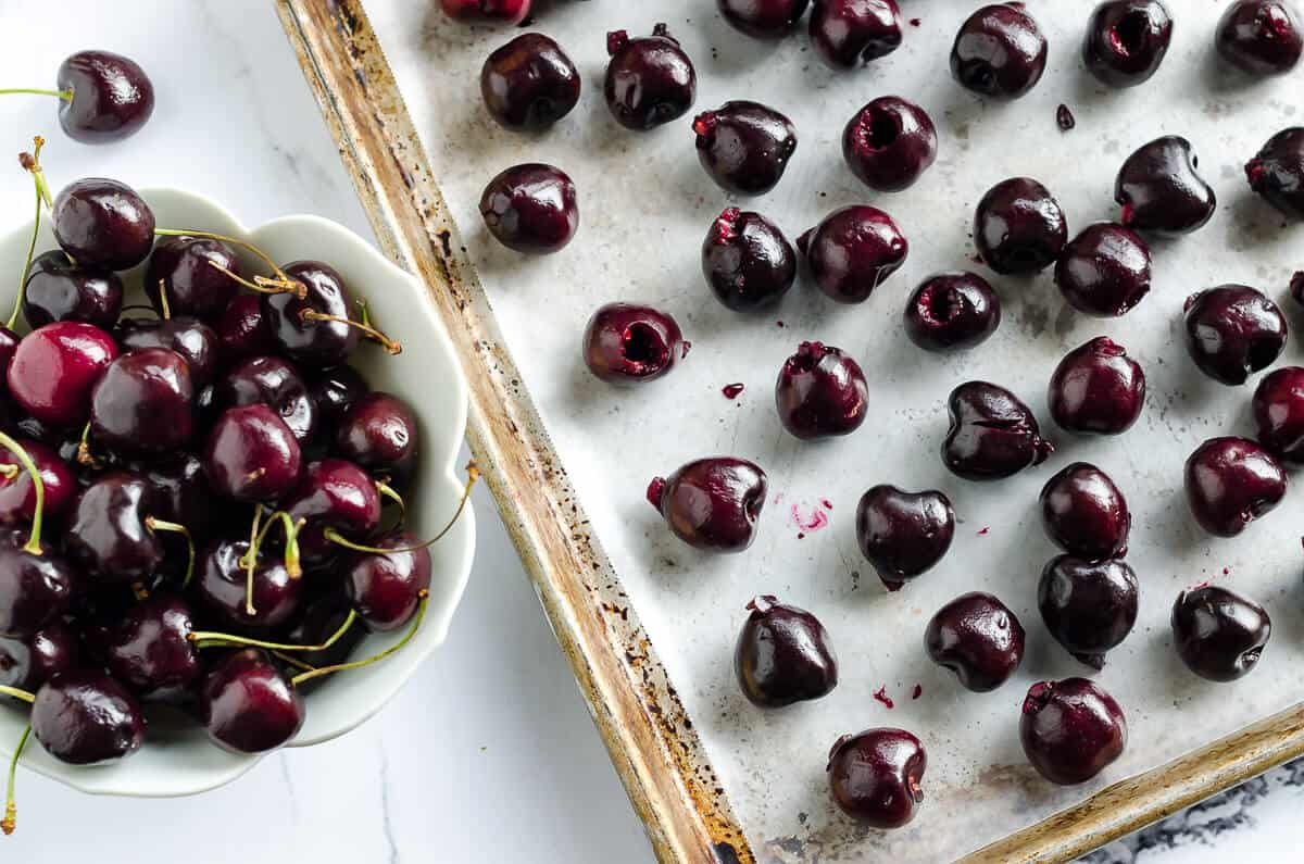 bowl of fresh sweet cherries next to a sheet pan with pitted cherries spread out for how to freeze cherries