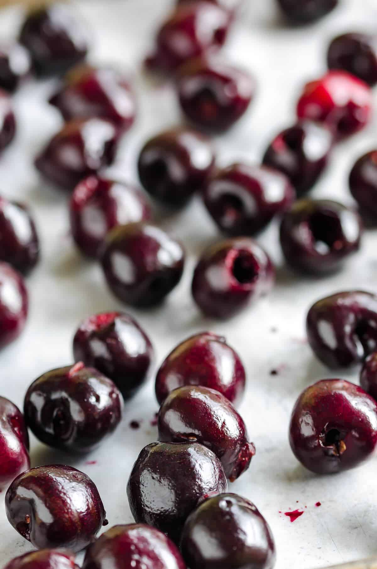 deep red fresh pitted cherries spread out on a sheet pan for freezing cherries