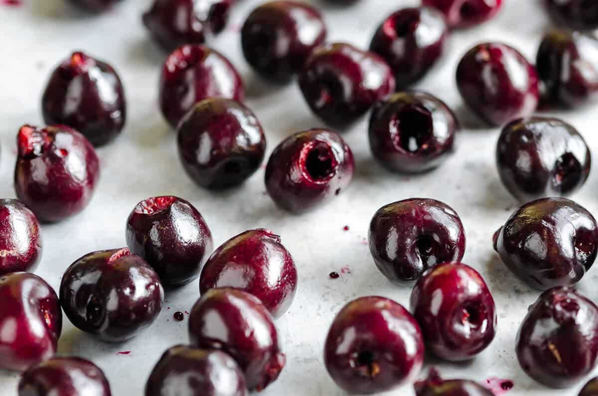 vibrant deep red fresh pitted cherries spread out on a sheet pan