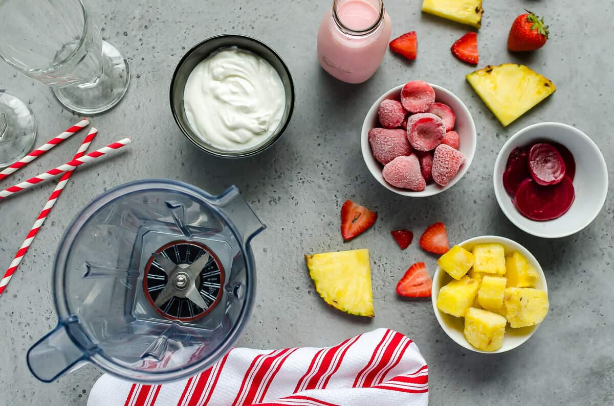ingredients for strawberry pineapple smoothie: yogurt, strawberry milk, frozen strawberries, frozen pineapple, beet juice, blender