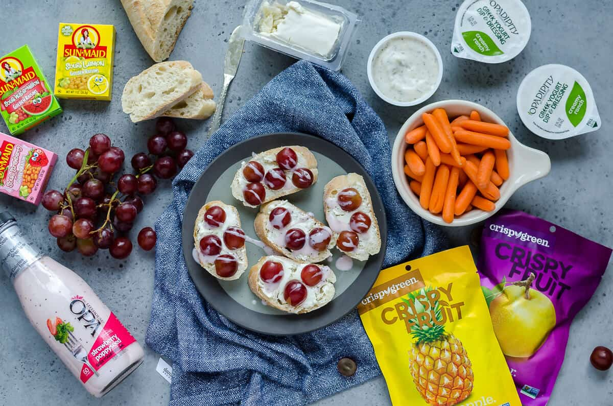 plate full of goat cheese crostini surrounded by healthy lunch options: carrots, ranch, sunmaid raisins, cluster of grapes and crispy fruit packages