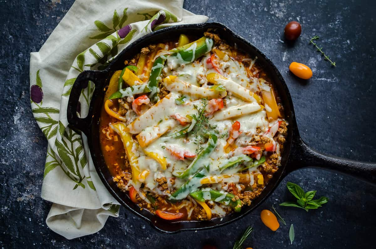 overhead view of a cast iron skillet filled with unstuffed peppers made with ground turkey, colored peppers and covered in melted cheese.