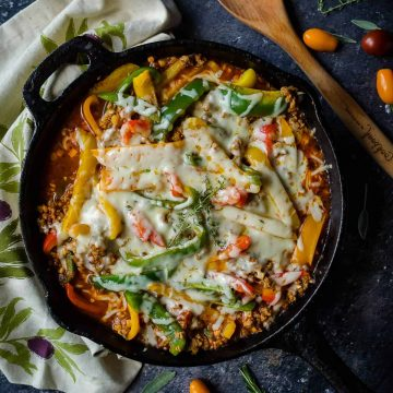 cast iron skillet of unstuffed peppers using ground turkey, colored bell peppers, cauli rice and melted cheese on top.