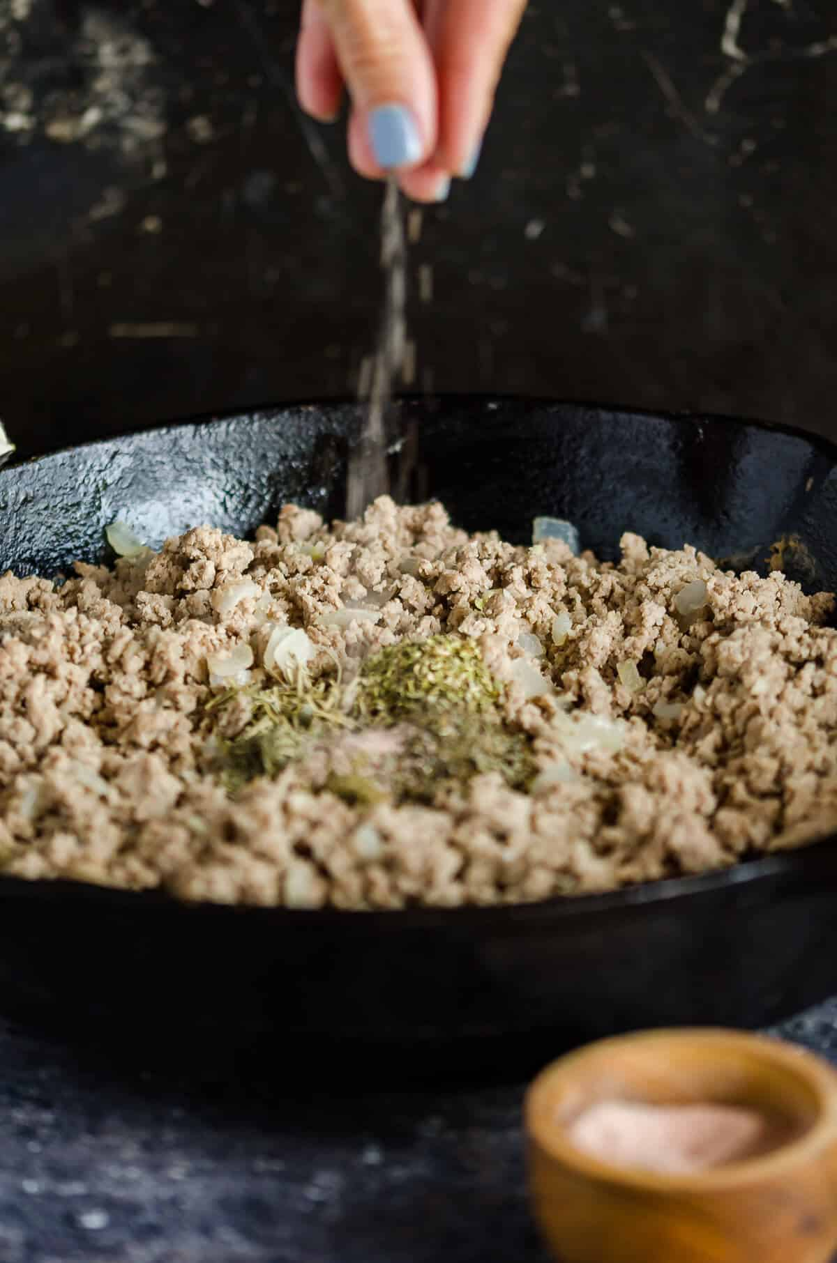 cast iron skillet filled with cooked ground turkey with seasonings and salt being sprinkled in