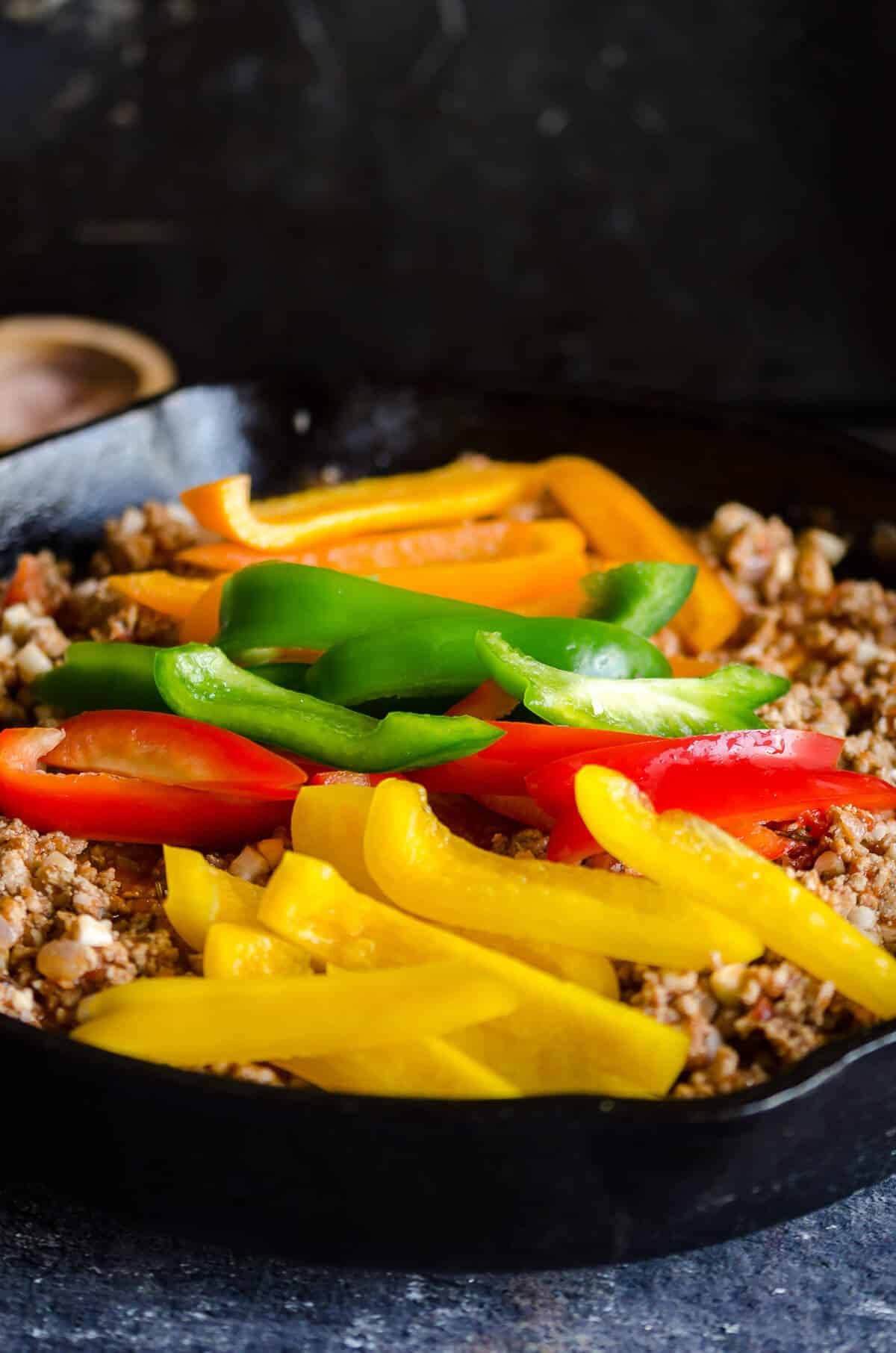 Cast iron skillet with ground turkey and slices of colored bell peppers