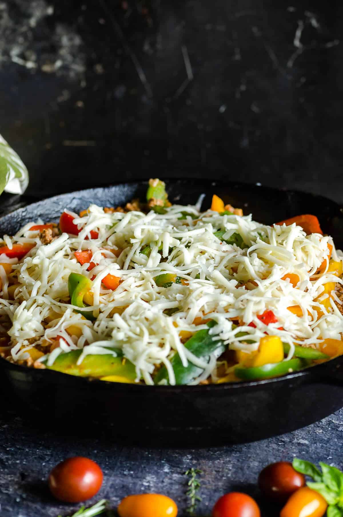 cast iron skillet filled with low carb unstuffed peppers made with ground turkey and cauli rice and sprinkled with cheese ready to go in the oven.