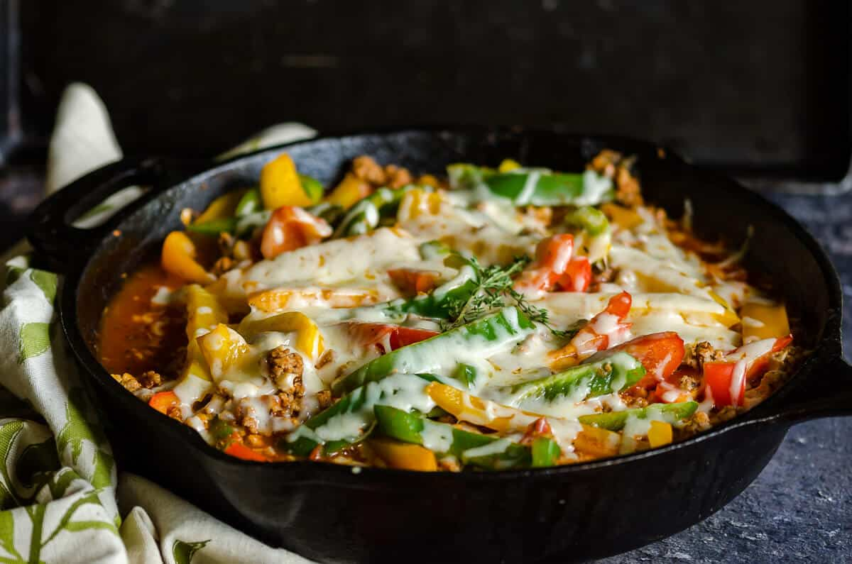 cast iron skillet filled with cooked ground turkey in an Italian sauce with sliced of colored bell peppers and melted cheese.