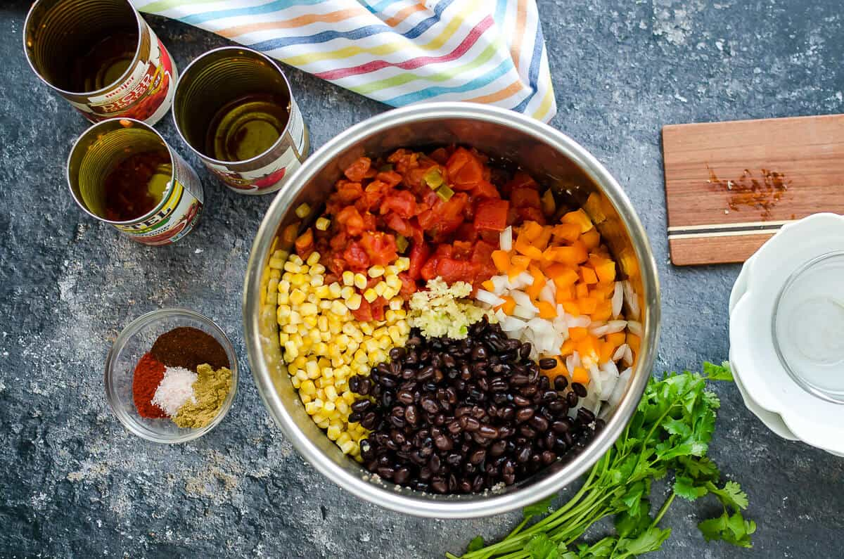 insert of instant pot filled with corn, black beans, onions, peppers and diced tomatoes