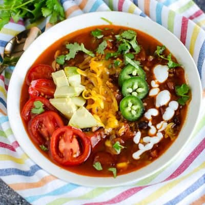 bowl of turkey taco soup garnished with sliced cherry tomatoes, avocados, cheese, jalapeños, and yogurt