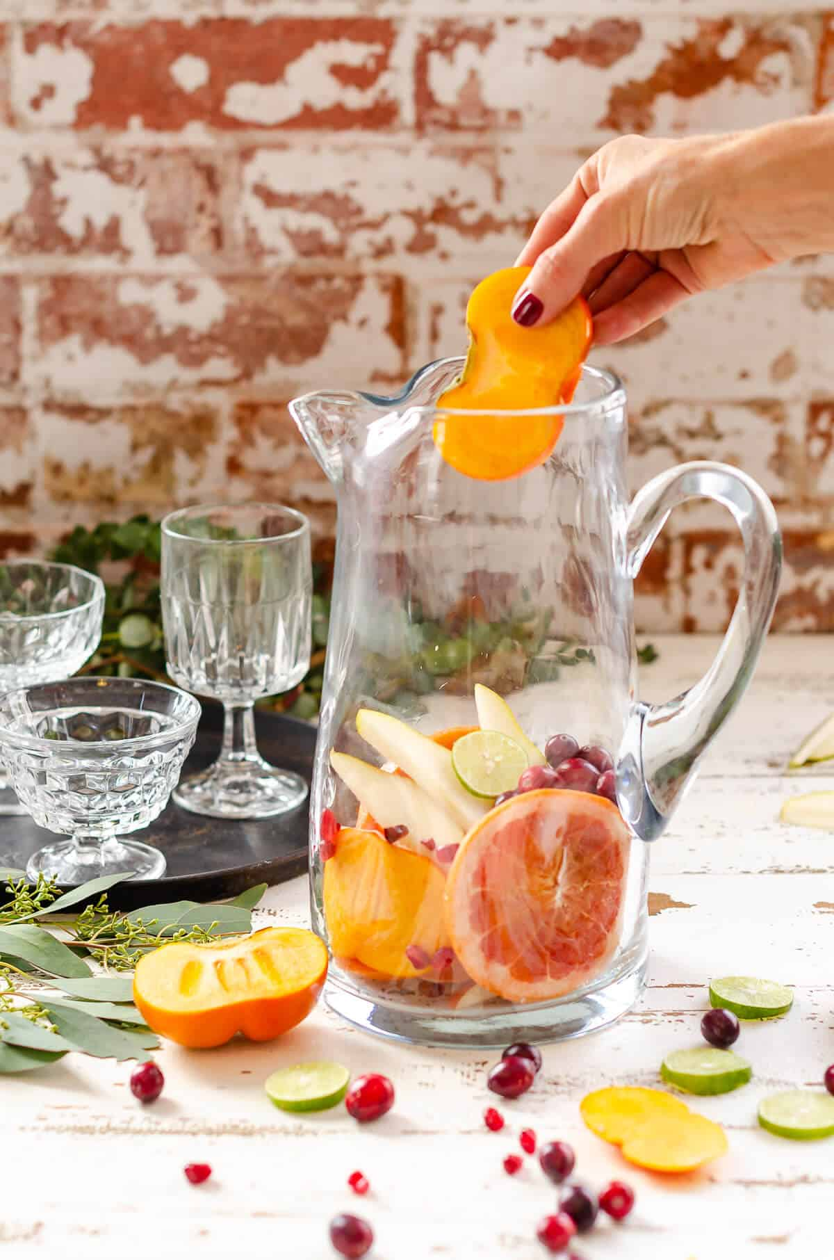 hand adding a slice of persimmon to a clear glass pitcher filled with fresh grapefruit, pears and cranberries for a Sangria Mocktail