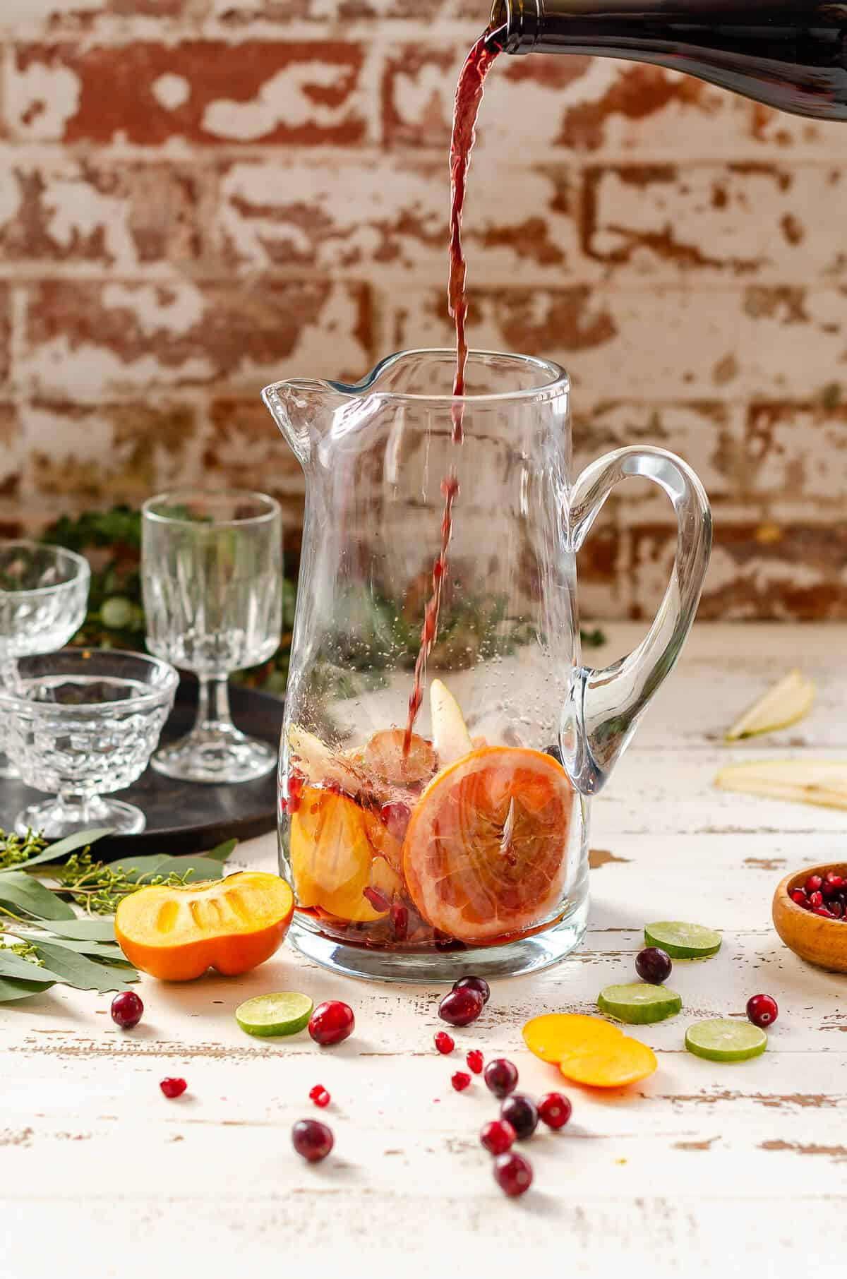 clear glass pitcher with grapefruit, persimmon, pears, and cranberries in the bottom, with red non-alcoholic wine being poured in.
