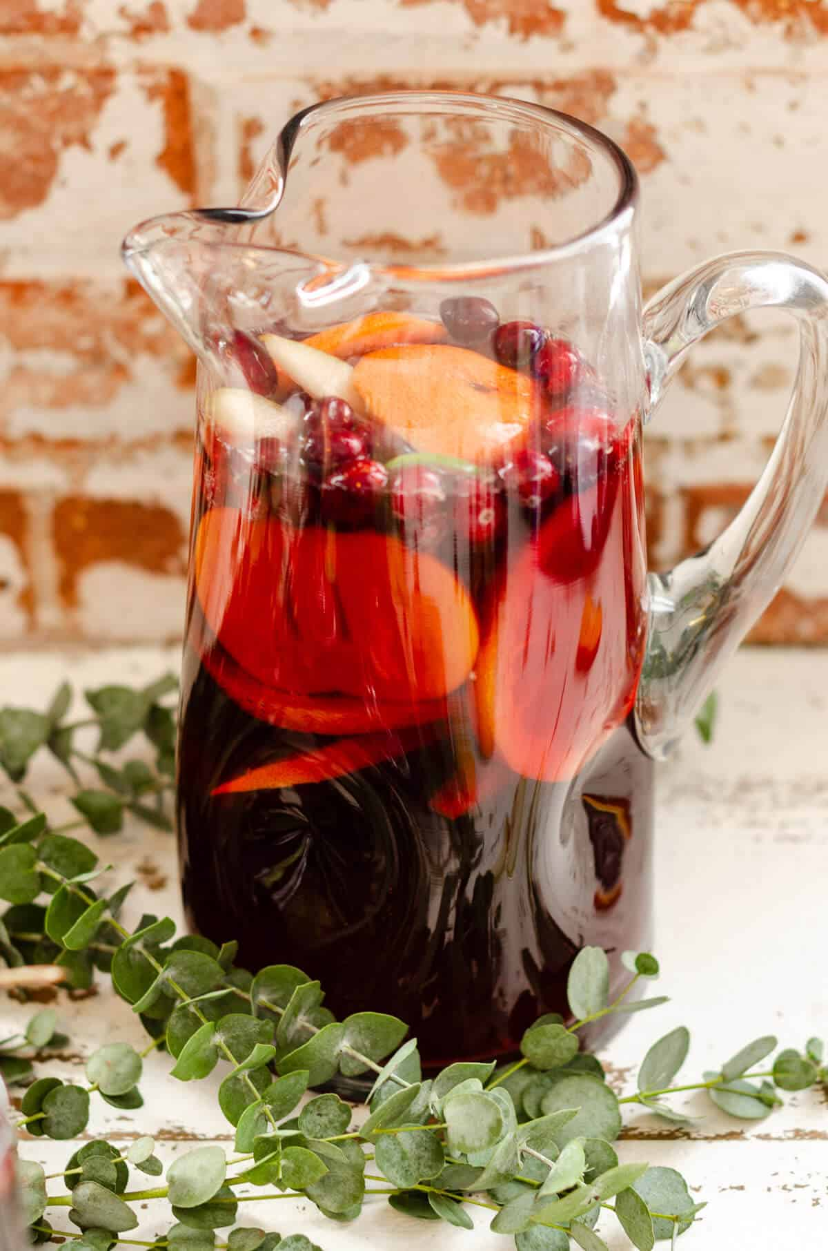 Clear glass pitcher filled with non alcoholic red sangria mocktail, fresh grapefruit, oranges, persimmon, and cranberries. greens surrounding the pitcher