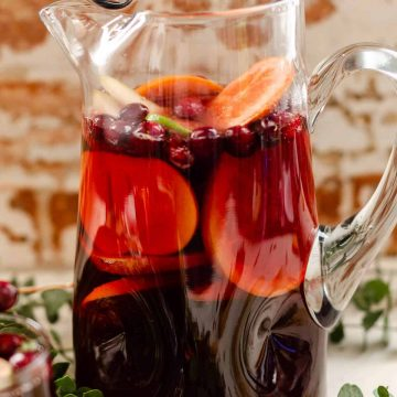 Clear glass pitcher filled with non alcoholic red sangria mocktail, fresh grapefruit, oranges, persimmon, and cranberries