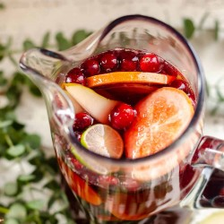 overhead view of a pitcher filled with red Sangria Mocktail, grapefruit, limes, pears and cranberries