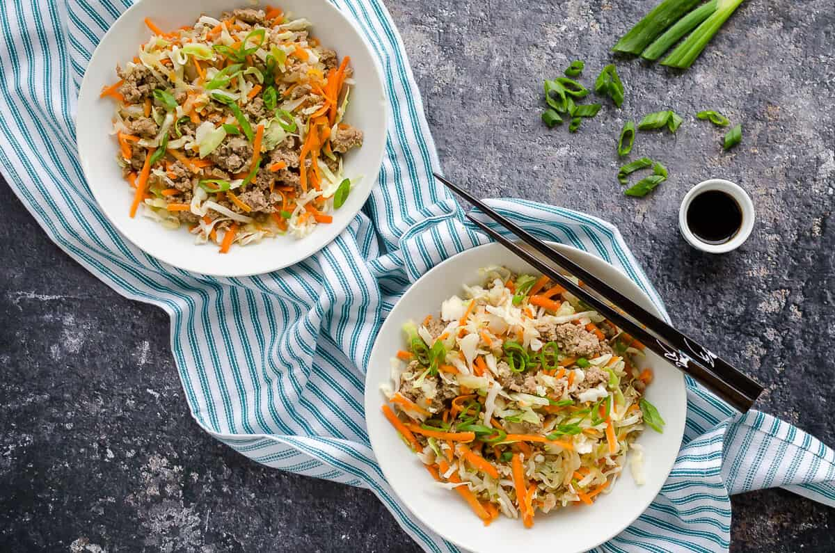 2 white bowls filled with cooked ground turkey, cole slaw and seasonings to form egg roll in a bowl (a deconstructed egg roll without the wrapper).