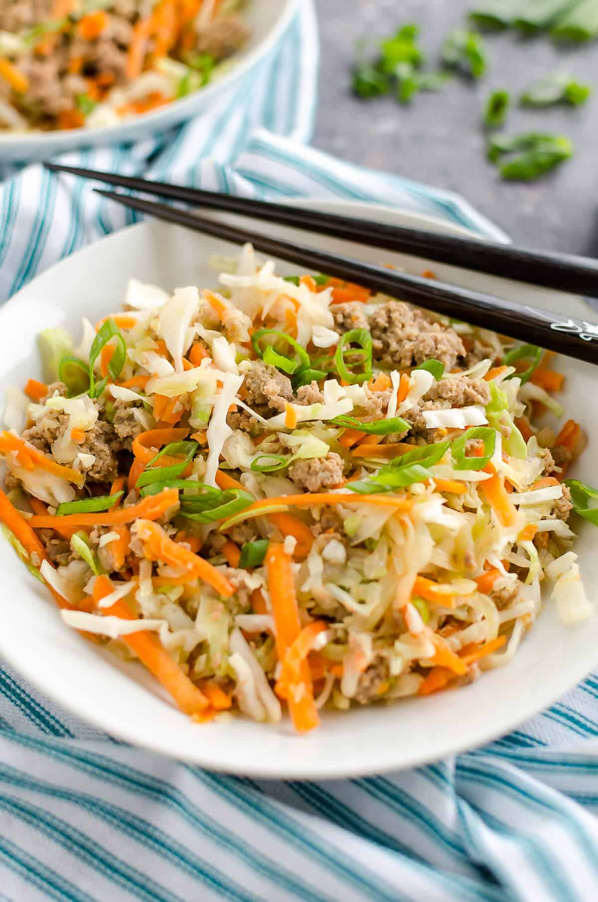white bowl filled with cooked ground turkey, shredded cabbage, shredded carrots and seasonings to create a deconstructed egg roll. chopsticks laying over top of the bowl.