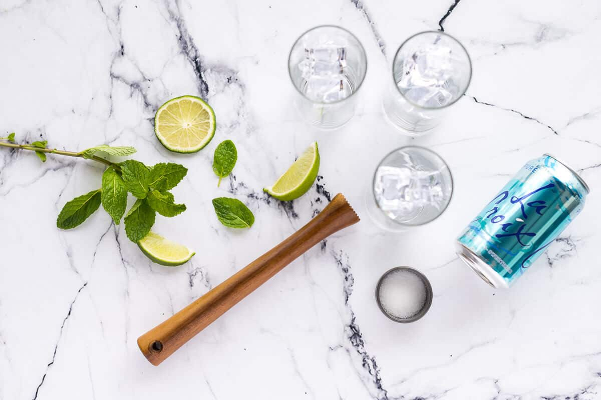 lime slices, mint leaves and a muddle for mojitos with 3 glasses of ice