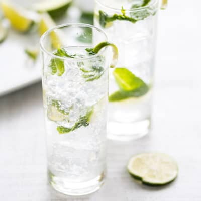 two mojito mocktails in clear glasses with fresh mint and lime