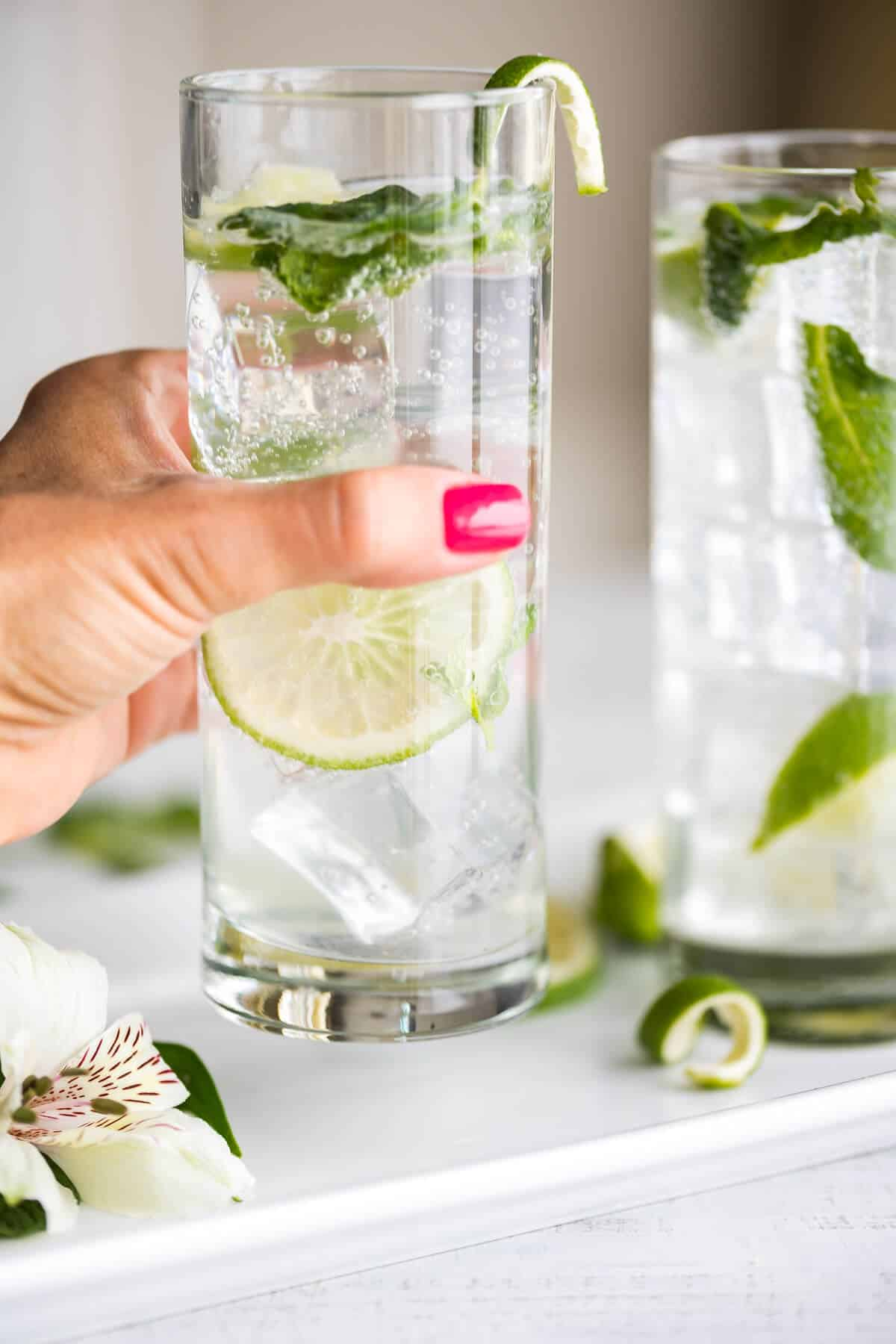hand lifting virgin mojito from a white tray