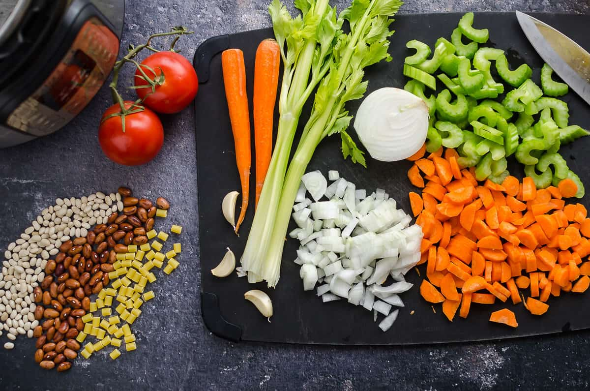 cutting board with chopped carrots, celery and onions along side dried beans, pasta and tomatoes