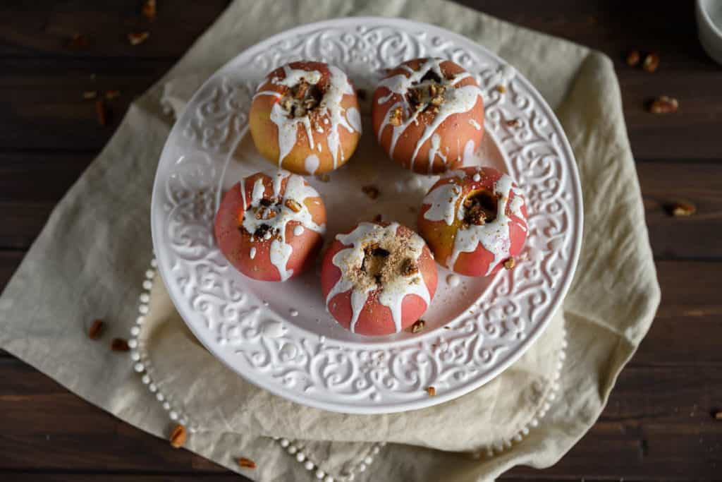 5 healthy baked apples on a white platter drizzled with yogurt sauce, chopped pecans and nutmeg
