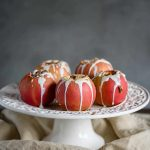 healthy baked apples drizzled with sweet yogurt sauce, pecans and cinnamon on a cake pedestal