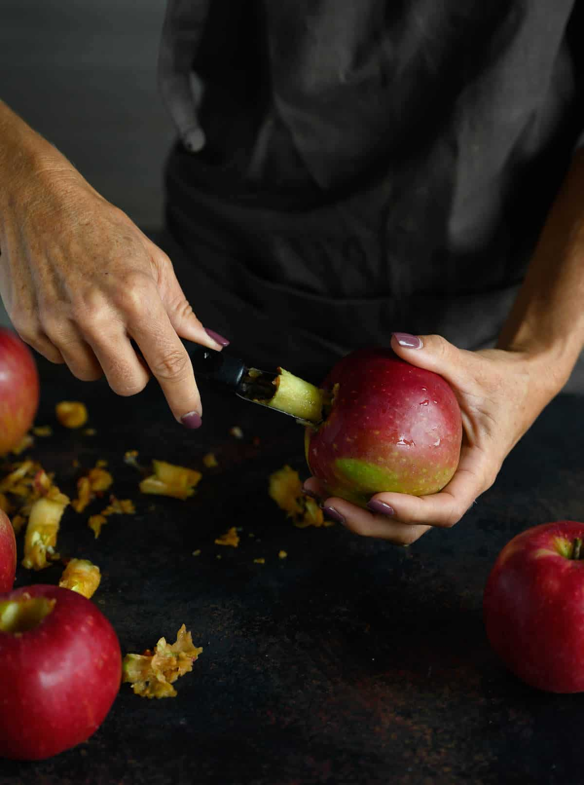 woman using an apple corer to remove the core of a whole apple