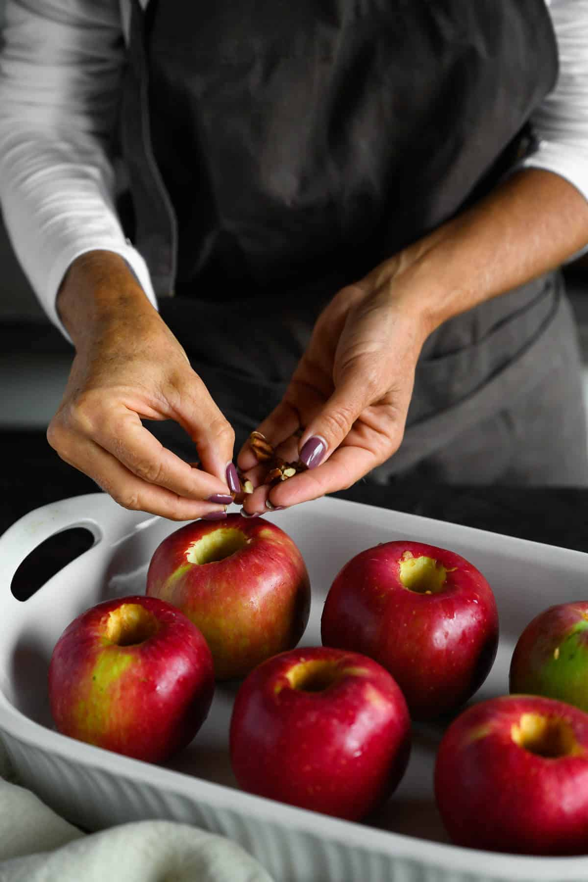 woman filling cored apples with chopped pecans