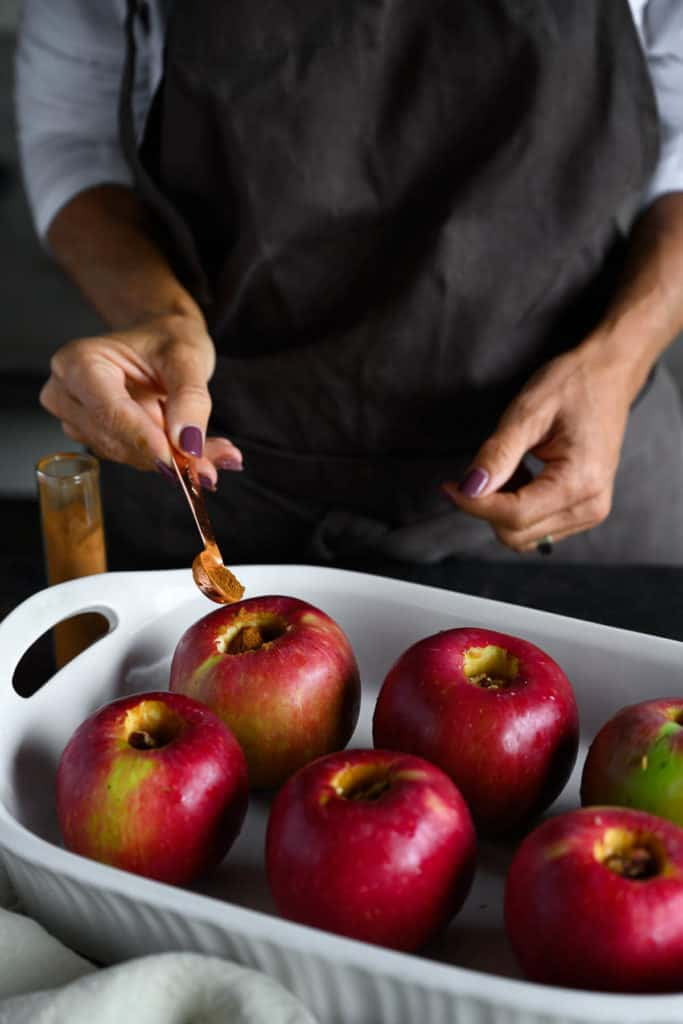 woman sprinkling cinnamon over whole cored apples for baking.