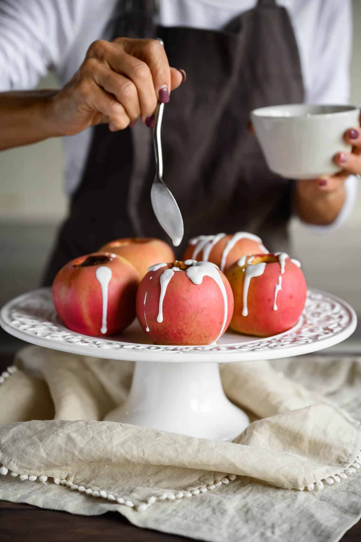 woman drizzling sweet yogurt sauce over baked apples on a white platter
