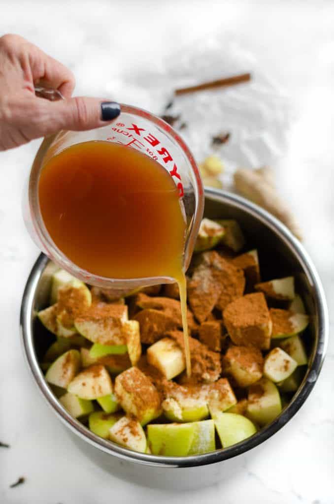apple cider being poured over apples and spices in an instant pot for apple butter