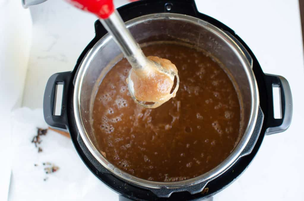 cooked apple butter in the instant pot with an immersion blender