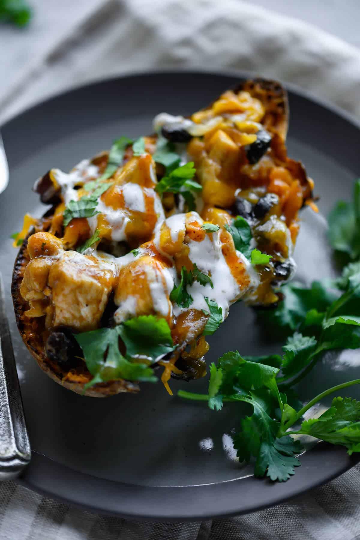 enchilada stuffed sweet potato on a plate garnished with cilantro