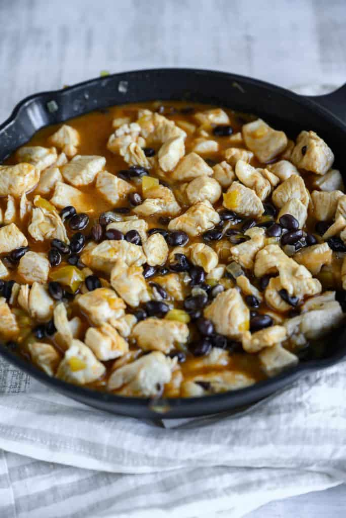 skillet with chicken, black beans, chili peppers and enchilada sauce